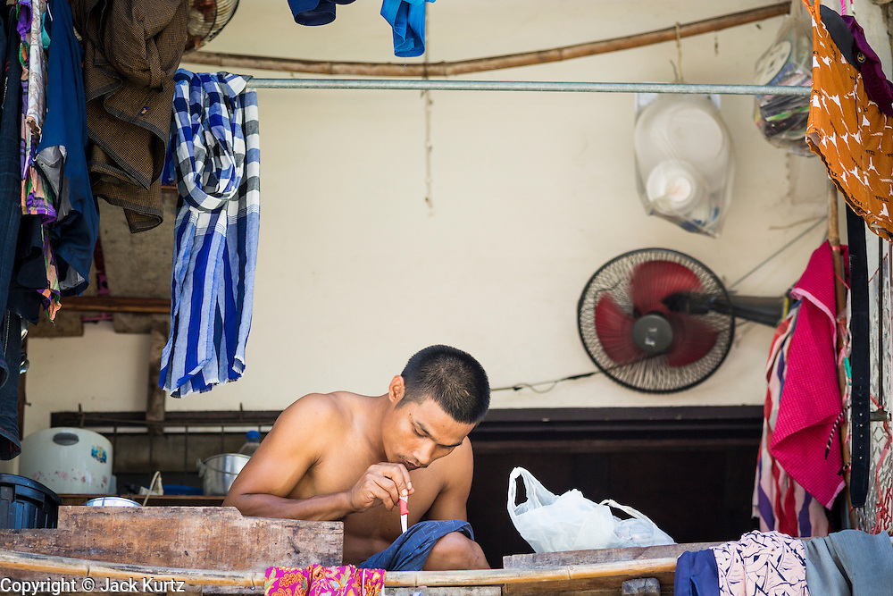 30 APRIL 2013 - MAHACHAI, SAMUT SAKHON, THAILAND: A Burmese man works on an appliance on a tenement balcony above a fish processing plant in Mahachai, Samut Sakhon province, Thailand. The Thai fishing industry is heavily reliant on Burmese and Cambodian migrants. Burmese migrants crew many of the fishing boats that sail out of Samut Sakhon and staff many of the fish processing plants in Samut Sakhon, about 45 miles south of Bangkok. Migrants pay as much $700 (US) each to be smuggled from the Burmese border to Samut Sakhon for jobs that pay less than $5.00 (US) per day. There have also been reports that some Burmese workers are abused and held in slavery like conditions in the Thai fishing industry.         PHOTO BY JACK KURTZ