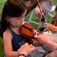 After watching fiddlers at the Merlefest picking tent this young child is introduced to the fiddle
