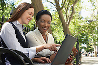 Two female colleagues using laptop on park bench