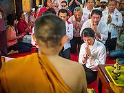 17 FEBRUARY 2013 - BANGKOK, THAILAND:   Thai Prime Minister YINGLUCK SHINAWATRA is blessed by a monk after she offered prayers for Pongsapat Pongchareon in Wat Chana Songkram in Bangkok Sunday. Pol General Pongsapat Pongcharoen, a former deputy national police chief who also served as secretary-general of the Narcotics Control Board is the Pheu Thai Party candidate in the upcoming Bangkok governor's election. Yingluck is the head of the Pheu Thai party and campaigns with Pongsapat. (He resigned from the police force to run for Governor.) Former Prime Minister Thaksin Shinawatra reportedly recruited Pongsapat. Most of Thailand's reputable polls have reported that Pongsapat is leading in the race and likely to defeat Sukhumbhand Paribatra, the Thai Democrats' candidate and incumbent. The loss of Bangkok would be a serious blow to the Democrats, whose base is the Bangkok area.    PHOTO BY JACK KURTZ