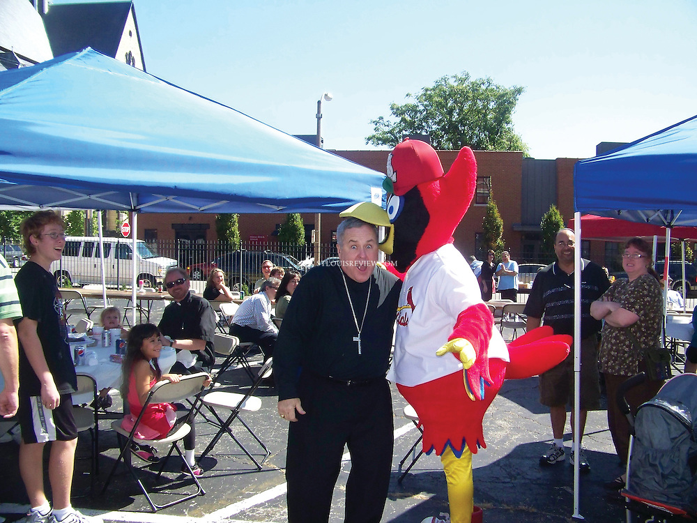 Archbishop Robert J. Carlson shared a fun moment with St. Louis Cardinals mascot Fredbird at a parish festival at Sts. Peter and Paul Parish in Soulard in September. The archbishop celebrated Mass at the parish that day in honor of its 160th anniversary. Afterward, he joined members of Peter and Paul Community Services Inc. to tour the organization's emergency shelter and learn more about the services it provides to the homeless.