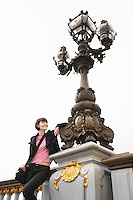 Young woman leaning on ornate streetlight