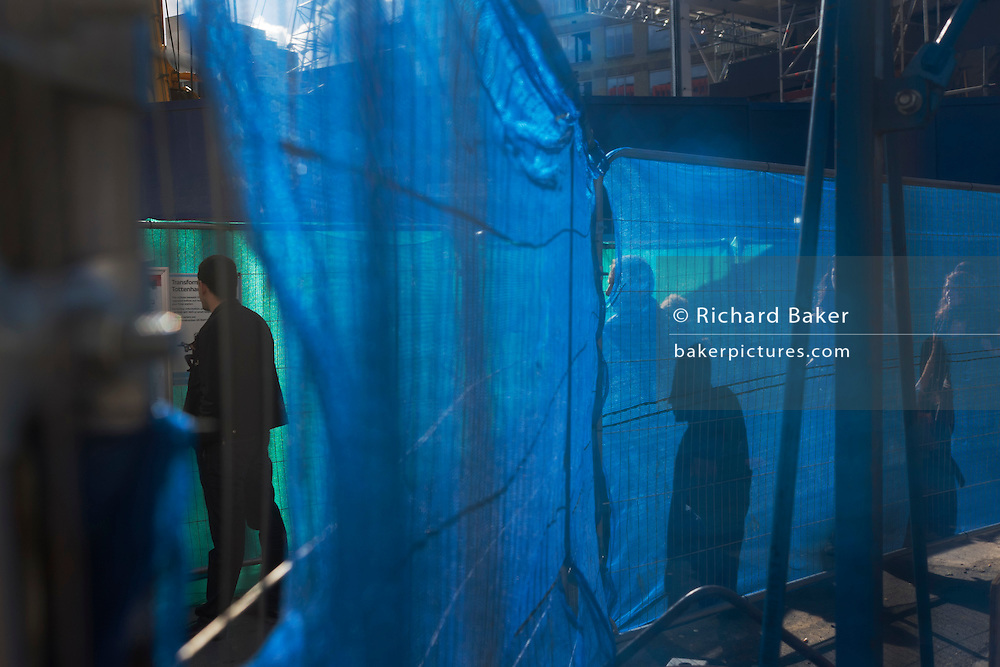 Pedestrian figures amid Jubilee Line construction backlit blue netting fences at Tottenham Court Road.