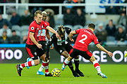 Allan Saint-Maximin (#10) of Newcastle United attempts to find a gap between the challenges of Cedric Soares (#2) of Southampton and James Ward-Prowse (#16) of Southampton during the Premier League match between Newcastle United and Southampton at St. James's Park, Newcastle, England on 8 December 2019.