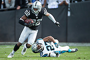 Oakland Raiders running back Taiwan Jones (22) slips through a Carolina Panthers tackle at Oakland Coliseum in Oakland, Calif., on November 27, 2016. (Stan Olszewski/Special to S.F. Examiner)