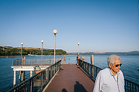 ANGUILLARA SABAZIA (LAKE BRACCIANO), ITALY - 26 JULY 2017: An elderly man walks on a jetty in Lake Bracciano, whose level has dropped more than 1,50 meters, in Anguillara Sabazia (Lake Bracciano), Italy, on July 26th 2017.<br /> <br /> Lake Bracciano provides eight percent of Rome's water and has sunk about 1.5 meters<br /> <br /> A severe drought and sweltering temperatures have led Rome city officials to consider a potential rationing of drinking water for eight hours a day for a million and a half Rome residents. The water crisis has become yet another sign of man being at the mercy of an increasingly extreme climate, but also of once mighty Rome's political impotence, managerial ineptitude and overall decline.
