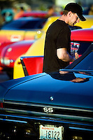 JEROME A. POLLOS/Press..James Almond walks between classic cars on display Friday at the River City Rod Run in Post Falls.