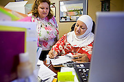 22 JUNE 2009 - PHOENIX, AZ: Aysar Jabar (left), a volunteer at the Cultural Cup helps founder Zarinah Awad in the office. Jabar translates from Arabic to English for clients at the Cultural Cup. The Cultural Cup has become a sort of community center. It started as a food bank and has since grown to include a clothing bank and free walk in clinic. The walk in clinic at the Cultural Cup Food Bank started two years ago when Cultural Cup founder Zarinah Awad wanted to expand the food bank's outreach and provide basic medical care for the people who use the food bank. The clinic sees, on average, 7 - 11 patients a week. Awad said that as the economy has worsened since the clinic opened and demand has steadily increased. She attributes the growth to people losing their jobs and health insurance. The clinic is staffed by volunteers both in the office and medical staff. Adults are seen every Saturday. Children are seen one Saturday a month, when a pediatrician comes in. Awad, a Moslem, said the food bank and clinic are rooted in the Moslem tradition of Zakat or Alms Giving, the giving of a small percentage of one's income to charity which is one of the Five Pillars of Islam.   PHOTO BY JACK KURTZ