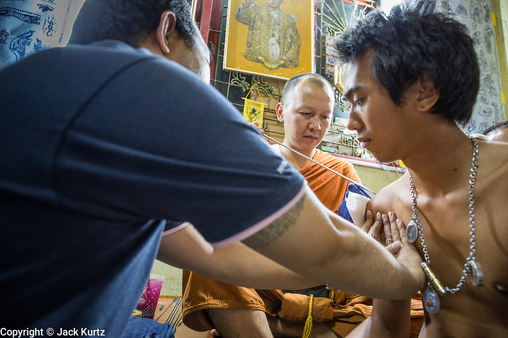 """22 MARCH 2013 - NAKHON CHAI SI, NAKHON PATHOM, THAILAND: A monk gives a man a sacred Sak Yant tattoo at Wat Bang Phra. Wat Bang Phra is the best known """"Sak Yant"""" tattoo temple in Thailand. It's located in Nakhon Pathom province, about 40 miles from Bangkok. The tattoos are given with hollow stainless steel needles and are thought to possess magical powers of protection. The tattoos, which are given by Buddhist monks, are popular with soldiers, policeman and gangsters, people who generally live in harm's way. The tattoo must be activated to remain powerful and the annual Wai Khru Ceremony (tattoo festival) at the temple draws thousands of devotees who come to the temple to activate or renew the tattoos. People go into trance like states and then assume the personality of their tattoo, so people with tiger tattoos assume the personality of a tiger, people with monkey tattoos take on the personality of a monkey and so on. In recent years the tattoo festival has become popular with tourists who make the trip to Nakorn Pathom province to see a side of """"exotic"""" Thailand. The 2013 tattoo festival was on March 23.    PHOTO BY JACK KURTZ"""