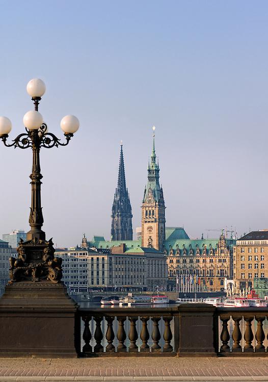 An der Alster im Frühjahr bei sonnigem Wetter. Der Rathausturm und die Nikolaikirche von der Lombardsbrücke aus gesehen.
