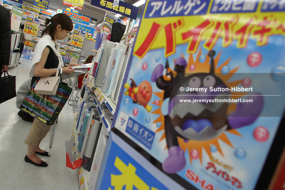 Customers in 'Bic' Store, Yurakacho, Tokyo, shopping for 'white' products such as fridges, air conditioning units, hair curling tongs and electronic toliet seats which all claim to have negative ion health benefits and properties.