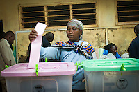 Agnes Muthoni Ngemu (left) casts the first ballot at Olympic Primary School Polling Station, Kibera, Nairobi, Kenya. She had been there since 4:30 in the morning.