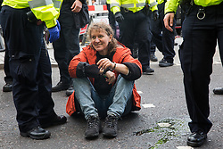 London, UK. 16 October, 2019. Police officers arrest a climate activist from Extinction Rebellion who had defied the Metropolitan Police prohibition on Extinction Rebellion Autumn Uprising protests throughout London under Section 14 of the Public Order Act 1986 by glueing herself to the road in Whitehall.