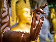 "12 NOVEMBER 2012 - BANGKOK, THAILAND:   The hand of a Buddha statue on Bamrung Muang Street in Bangkok. Thanon Bamrung Muang (Thanon is Thai for Road or Street) is Bangkok's ""Street of Many Buddhas."" Like many ancient cities, Bangkok was once a city of artisan's neighborhoods and Bamrung Muang Road, near Bangkok's present day city hall, was once the street where all the country's Buddha statues were made. Now they made in factories on the edge of Bangkok, but Bamrung Muang Road is still where the statues are sold. Once an elephant trail, it was one of the first streets paved in Bangkok. It is the largest center of Buddhist supplies in Thailand. Not just statues but also monk's robes, candles, alms bowls, and pre-configured alms baskets are for sale along both sides of the street.    PHOTO BY JACK KURTZ"