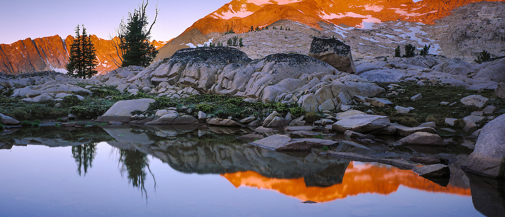 Cramer Peak, one of the highest peaks in the Sawtooth Mountain Range, reflects into a  high mountain pond.