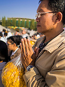 "02 JANUARY 2015 - KHLONG LUANG, PATHUM THANI, THAILAND: A man prays at Wat Phra Dhammakaya at the start of the 4th annual Dhammachai Dhutanaga (a dhutanga is a ""wandering"" and translated as pilgrimage). More than 1,100 monks are participating in a 450 kilometer (280 miles) long pilgrimage, which is going through six provinces in central Thailand. The purpose of the pilgrimage is to pay homage to the Buddha, preserve Buddhist culture, welcome the new year, and ""develop virtuous Buddhist youth leaders."" Wat Phra Dhammakaya is the largest Buddhist temple in Thailand and the center of the Dhammakaya movement, a Buddhist sect founded in the 1970s.   PHOTO BY JACK KURTZ"