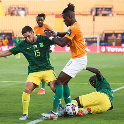 24 June 2019, Egypt, Cairo: Ivory coast's Wilfried Zaha (C) battles for the ball with South Africa's Thamsanqa Mkhize (R) and Dean Furman during the 2019 Africa Cup of Nations Group D soccer match between South Africa and Ivory coast at Al-Salam Stadium. Photo : PictureAlliance / Icon Sport