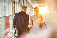 Rear view of businessman and businesswoman walking and talking
