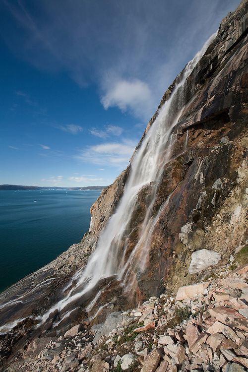 Greenland, Ilulissat, Waterfall cascades down steep granite fjord walls along Ata Sund in Disko Bay along western coastline on clear summer day