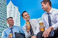 Group of colleagues sitting and talking while drinking coffee after work