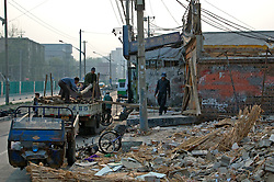China, Beijing, Chaoyang, San Jian Fang, 2008. Working with only sledgehammers and flatbed trucks, demolition crews make short work of structure built mostly of brick. What little steel reinforcement bar there is will be salvaged.
