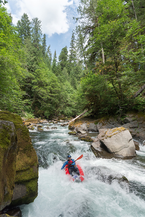 Paddling an inflatable kayak down a rapid on Salmon Creek, Oregon.