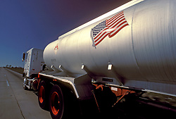 Large liquid transport truck with an American flag travelling down the highway in the afternoon