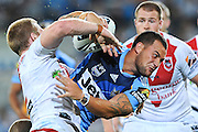 GOLD COAST, AUSTRALIA - MARCH 12:  Bodene Thompson of the Titans is tackled during the round one NRL match between the Gold Coast Titans and the St George Illawarra Dragons at Skilled Park on March 12, 2011 on the Gold Coast, Australia.  (Photo by Matt Roberts/Getty Images)
