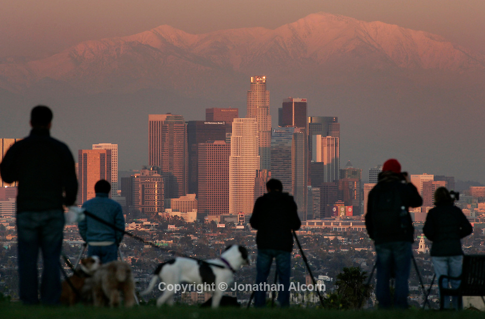People gather at Kenneth Hahn State Recreation Area to watch sunset over Downtown Los Angeles with the snow capped San Gabriel Mountains looming in the background the day after another in a series of strong winter storms hit the Southern California region.