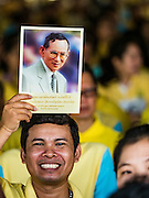 09 JUNE 2016 - BANGKOK, THAILAND: A man holds a picture of Bhumibol Adulyadej, the King of Thailand, over his head during a prayer after the merit making ceremony at the Grand Palace. Thailand marked 70 years of the reign of Bhumibol Adulyadej, with a special alms giving ceremony for 770 monks in front of the Grand Palace in Bangkok. The King, also known as Rama IX, ascended the throne on 9 June 1946. He is the longest serving monarch in Thai history and the longest serving monarch in the world today. He is revered by most Thais and is widely seen as a unifying figure in the country.     PHOTO BY JACK KURTZ