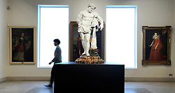 © Licensed to London News Pictures. 01/12/2011, London, UK. A Bonhams employee walks past a very rare 82cm high porcelain figure of Hercules created at the Doccia factory in Tuscany in 1753-55 is to be sold at Bonhams, New Bond Street, London on 7th December 2011.  This is the first time that a Doccia figure of this size has come to auction and the piece is estimated to sell for £300,000-500,000.. Photo credit : Stephen Simpson/LNP