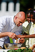 (photo by Matt Roth).Wednesday, October 21, 2009.Assignment ID: 30087135A..White House Assistant Chef Sam Kass shows students from nearby schools how to crack an egg during The White House Healthy Kids Fair on the South Lawn Wednesday, October 21, 2009. Before becoming the assistant White House chef, the twenty-nine-year-old was the Obamas' personal chef.