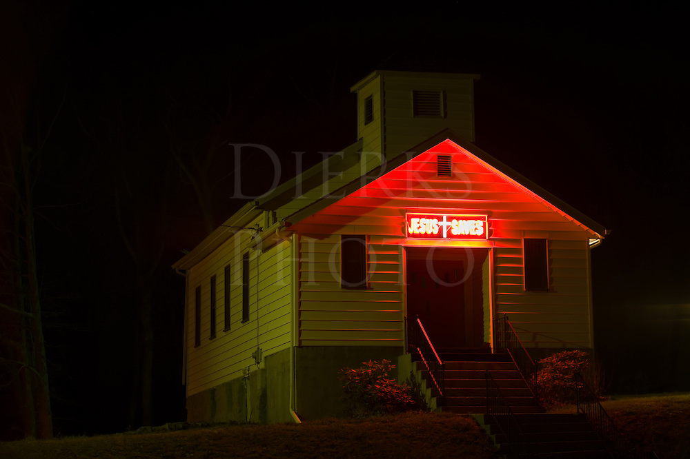 "Red neon ""Jesus Saves"" sign above a church door glowing in the dark night, the Bible Belt in Pennsylvania, PA, USA."
