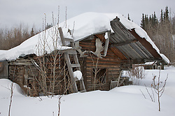 An empty cabin is snowed in at the ghost town of Old Bettles, Alaska.