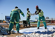 Constructiewerkers leggen decoratiestenen bij een nieuwe rotonde bij het vliegveld van Port Elizabeth, WK 2010 Zuid Afrika.