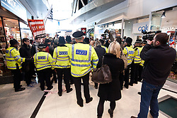 © licensed to London News Pictures. London, UK. 3/03/12. Demonstrators inside Plaza Shopping Centre, Oxford Street. Groups take part in a direct action protest against the controversial 'workfare' scheme where demonstrators claim benifit claimants are forced to work unpaid for participating companies. Photo credit: Jules Mattsson/LNP JMA