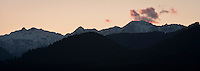 a red cloud forms bathed in evening alpenglow at twilight above an Olympic Mountain Peak in Olympic National Park, Washington State. panorama