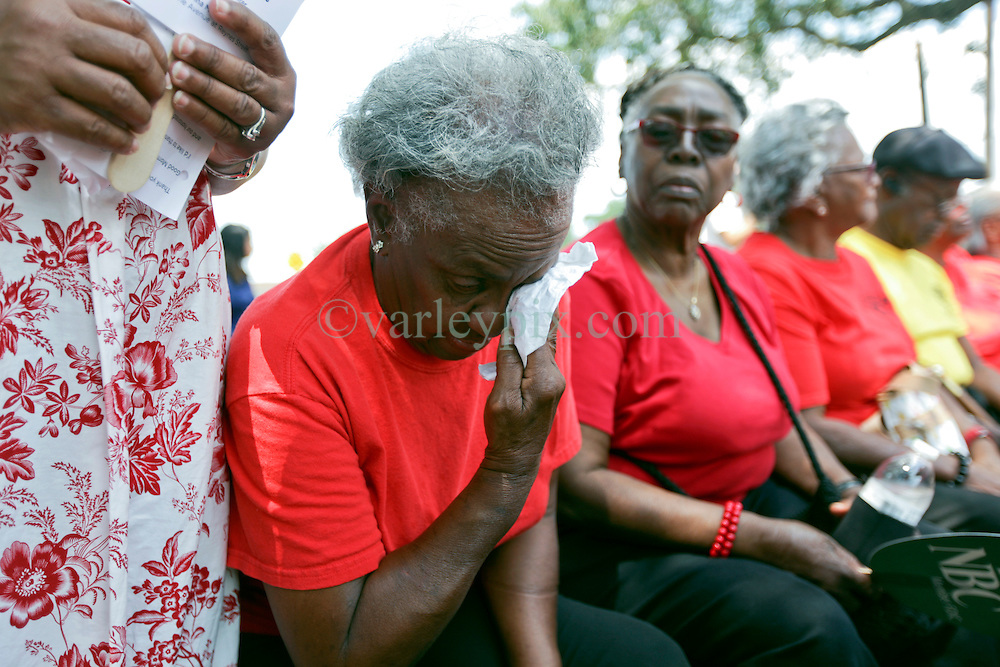 29 August 2015. Lower 9th Ward, New Orleans, Louisiana.<br /> Hurricane Katrina 10th anniversary memorials.  <br /> An elderly Katrina survivor wipes a tear from her eye during the memorial service. <br /> Photo credit&copy;; Charlie Varley/varleypix.com.