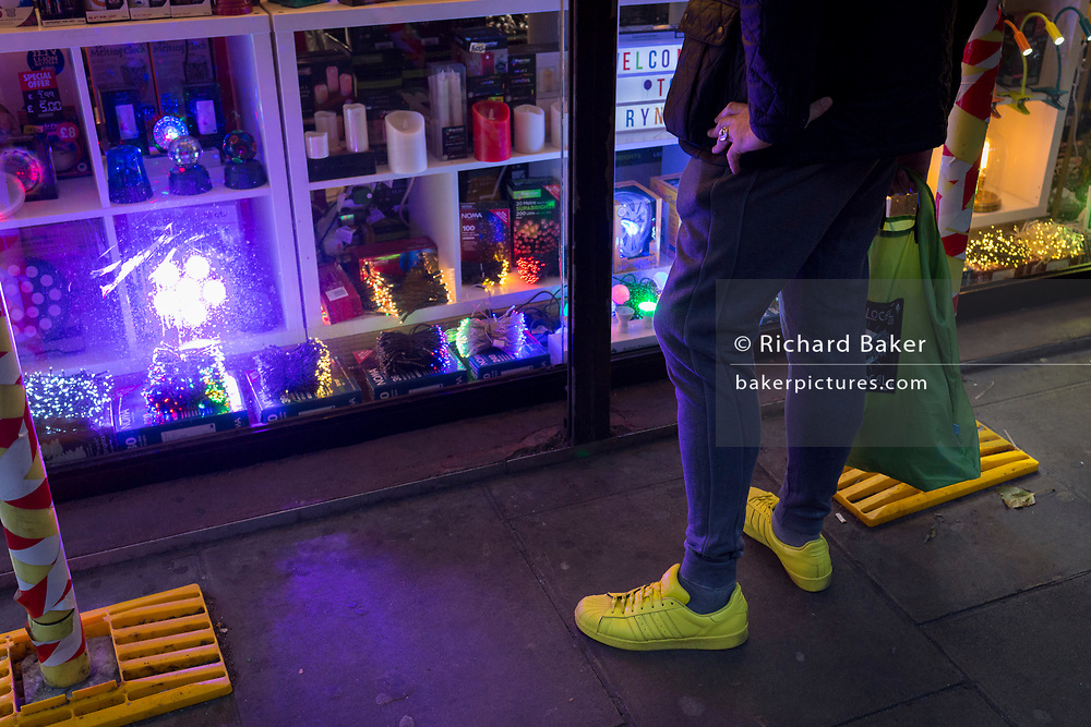 A man wearing yellow shoes stops to window shop in Soho, on 22nd November 2017, in London England.