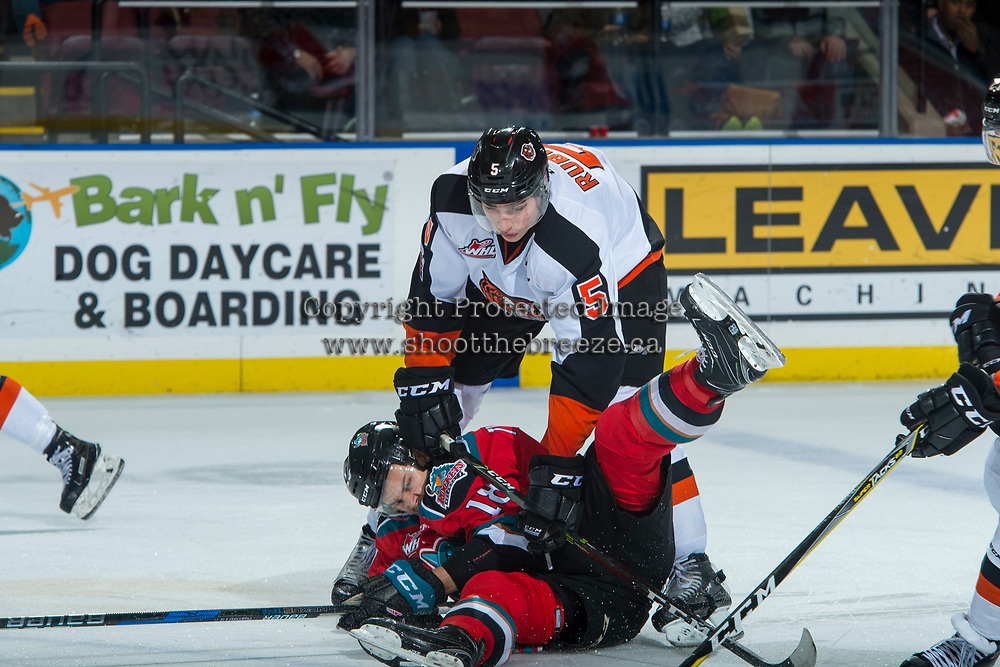 KELOWNA, CANADA - NOVEMBER 25: Kristians Rubins #5 of the Medicine Hat Tigers checks Carsen Twarynski #18 of the Kelowna Rockets during second period on November 25, 2017 at Prospera Place in Kelowna, British Columbia, Canada.  (Photo by Marissa Baecker/Shoot the Breeze)  *** Local Caption ***