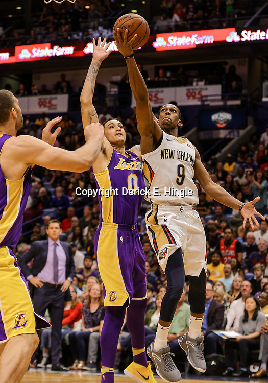 Mar 22, 2018; New Orleans, LA, USA; New Orleans Pelicans guard Rajon Rondo (9) shoots over Los Angeles Lakers forward Kyle Kuzma (0) and center Brook Lopez (left) during the fourth quarter at the Smoothie King Center. The Pelicans defeated the Lakers 128-125. Mandatory Credit: Derick E. Hingle-USA TODAY Sports