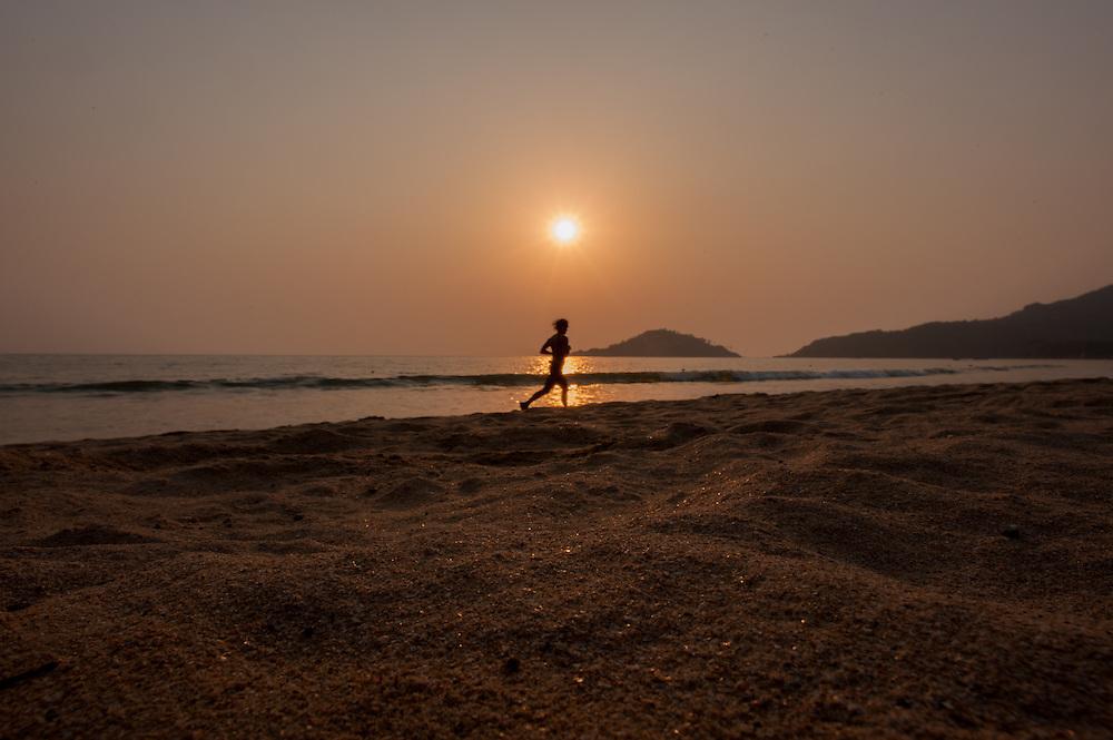 Man running on the beach at sunset in Goa (India)