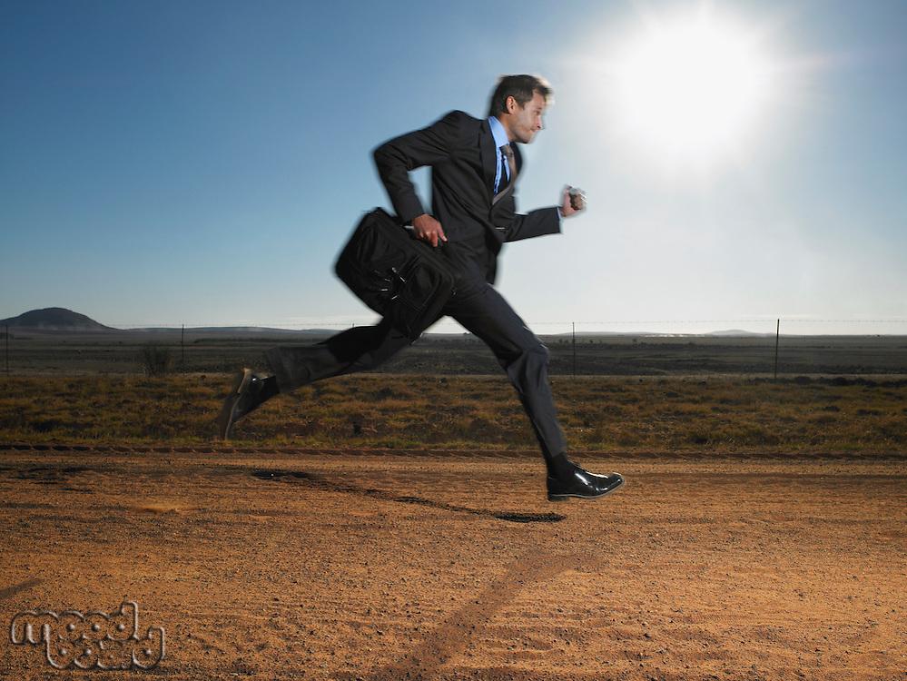Businessman Running Down Deserted Road