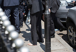© Licensed to London News Pictures. 19/06/2017. London, UK. Prime Minister Theresa May briefly stands barefoot on the pavement outside Finsbury Park Mosque after tripping and losing her shoe on arrival. Earlier a van ploughed into a crowd near Finsbury Park Mosque, as they finished taraweeh, Ramadan evening prayers. One person has been killed and 10 people are injured. Photo credit: Peter Macdiarmid/LNP