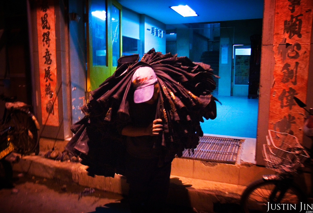 "A worker carries a pile of jeans in Zhongshan city, China, from a factory with Chinese good-luck banners on the gate.  .This picture is part of a photo and text story on blue jeans production in China by Justin Jin. .China, the ""factory of the world"", is now also the major producer for blue jeans. To meet production demand, thousands of workers sweat through the night scrubbing, spraying and tearing trousers to create their rugged look. .At dawn, workers bundle the garment off to another factory for packaging and shipping around the world..The workers are among the 200 million migrant labourers criss-crossing China.looking for a better life, at the same time building their country into a.mighty industrial power."