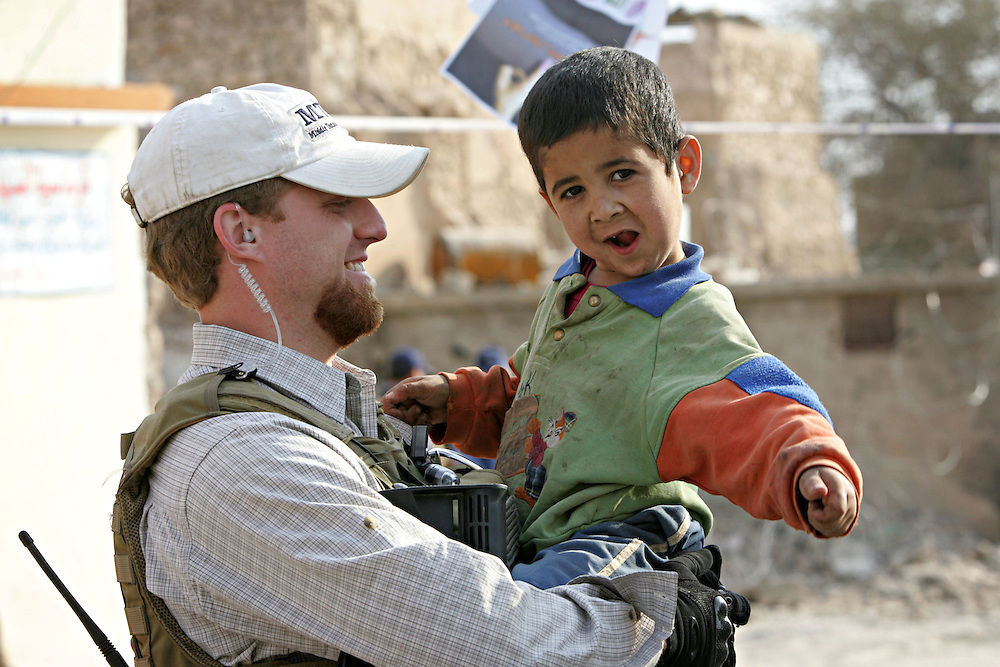 A private security contractor working for BlackWater picks up a young Iraqi boy during elections in Tal Afar, Norther Iraq on the 15th of december 2005