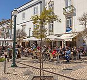 People sitting in sunshine outside street cafes in Praca da Republica, Tavira, Algarve, Portugal, Southern Europe