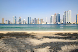 Daytime skyline view of beach and modern high-rise apartment buildings along Corniche in Sharjah United Arab Emirates