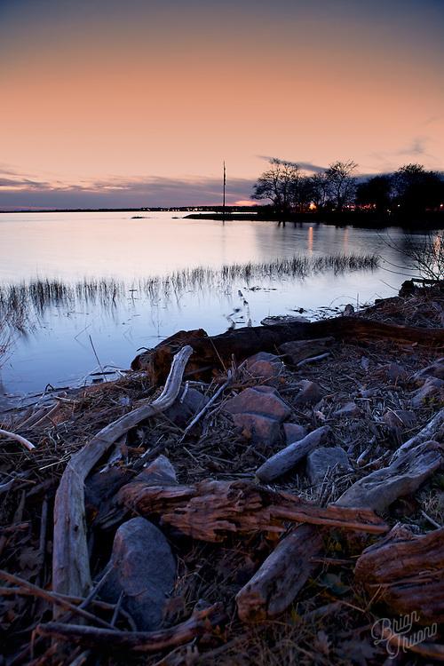Debris piled up along side the Delaware River at sunset.