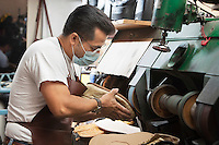 Skilled cobbler polishing show sole in machinery